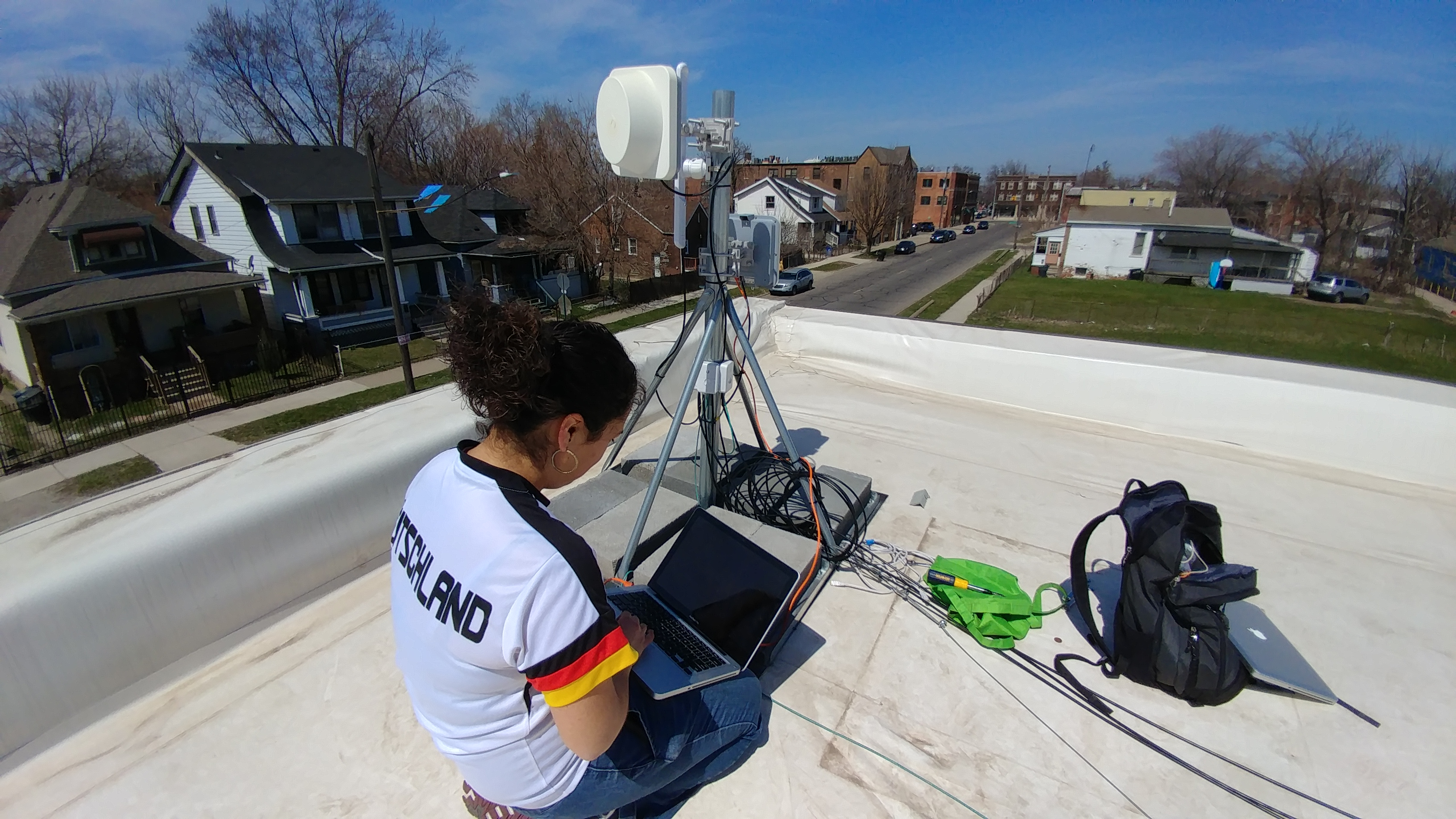 a digital steward on a rooftop, holding a laptop and setting up a large wireless antenna.